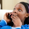 Astonished afro-american teenager talking on phone — Stock Photo #10828552