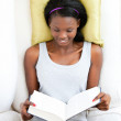 Bright female teenager reading a book lying on a sofa — Stock Photo