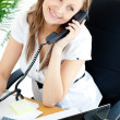 Bright businesswoman talking on phone sitting in her office — Stock Photo #10828713