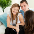Smiling couple listen to a saleswoman siting on a sofa — Stock Photo