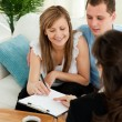 Bright young couple signing a contract sitting in their living r — Stock Photo