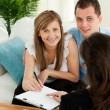 Loving young couple signing contract sitting in living roo — Stock Photo #10828748