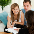 Loving young couple signing contract sitting in living roo — Foto Stock #10828748
