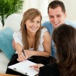 Happy young couple signing a contract sitting in the living room — Stock Photo