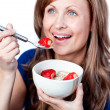 Positive young woman eating cereals with strawberries — 图库照片