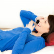 Surprised female teenager talking on phone lying on a sofa — Stock Photo #10828842