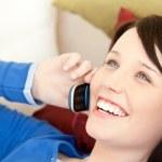 Cheerful female teenager talking on phone lying on a sofa — Stock Photo #10828846