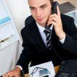 Caucasian young businessman talking on phone sitting at his desk — Stock Photo