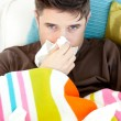 Stock Photo: Diseased young mwith tissues lying on sofa
