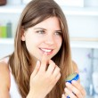 Pretty woman using vaseline for her lips — Stock Photo #10829264