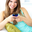 Smiling young woman texting sitting on the sofa - Stock Photo
