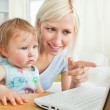 Blond mother having fun with her daughter in front of the laptop — Stock Photo #10829380