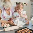 Smiling woman baking cookies with her daughters — Stock Photo #10829399