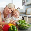 Smiling mother and daughter preparing a salad in kitchen — Stock Photo
