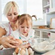 Focused woman baking cookies with her daughter — Stock Photo