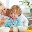Stock Photo: Mother having breakfast with her daughter