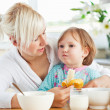 Attractive mother having breakfast with her daughter — Stock Photo