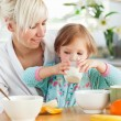 Radiant woman having breakfast with her daughter — Stock Photo