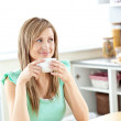 Blond caucasian woman drinking coffee in the kitchen — Stock Photo
