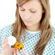 Concentrated female patient looking at her pills — Stock Photo #10829779