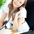 Self-assured businesswoman talking on phone sitting at her desk — Stock Photo