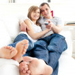 Young happy couple watching tv lying on the sofa — Stock Photo