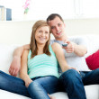 Affectionate man embracing his girlfriend while watching tv — Stock Photo