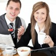 Royalty-Free Stock Photo: Joyful couple of businesspeople having breakfast smiling at the