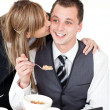 Beautiful blond businesswoman giving her smiling boyfriend a kis — Stock Photo
