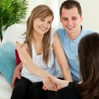 Happy couple concluding a contract with a female dealer — Stock Photo
