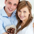 Stock Photo: Hugging couple holding chocolote smiling at camera