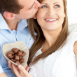 handsome man kissing his girlfriend holding chocolote — Stock Photo