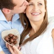 Handsome man kissing his girlfriend holding chocolote - 