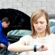 Man repairing car of pretty woman — Stock Photo