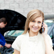 Man repairing car of phoning woman — Stock Photo