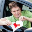 Happy young male driver tearing up her L sign — Stock Photo #10829979