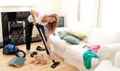 Enthusiastic woman in her chaotic living room — Stock Photo