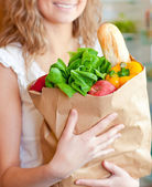 Femme souriante tenant un sac à provisions — Photo
