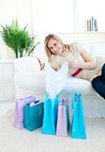 Cheerful woman lying on a couch with shopping bags — Stock Photo