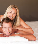 Young couple having fun together lying on bed — Stock Photo