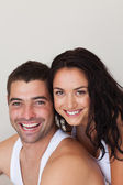 Blissful man with his girlfriend siiting on the bed — Stock Photo
