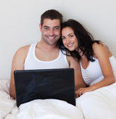 Enamoured couple using laptop — Stock Photo