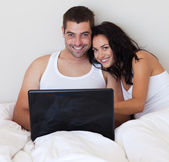 Jolly couple using a laptop at home — Stock Photo