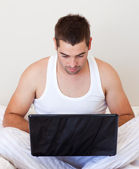Handsome man working on laptop at home — Stock Photo