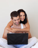 Romantic couple using a laptop lying — Stock Photo