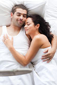 Young woman lying in bed with a boy — Stock Photo