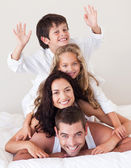 Smiling family climbing on top of each other — Foto de Stock