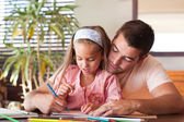 Little girl with her smiling father at the table — Stock Photo