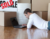 Young man lying on the floor in his new house — Stock Photo