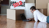 Beautiful man working at his laptop on the floor — Stock Photo